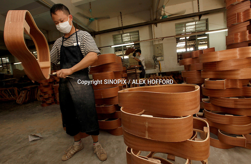 A worker makes a guitar at Australian guitar maker Bradley Clark's  factory in Bai Yun district, Guangzhou, Guangdong Province, China,  ..Photo by Alex Hofford / Sinopix.