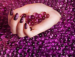Woman's hand with purple nail polish on abstract pink candy background