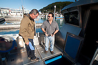 Bill Demonstrates to Duke how his Refrigerated Sea Water Hold Stores Fresh Caught Wild Salmon, Cordova, Alaska, US
