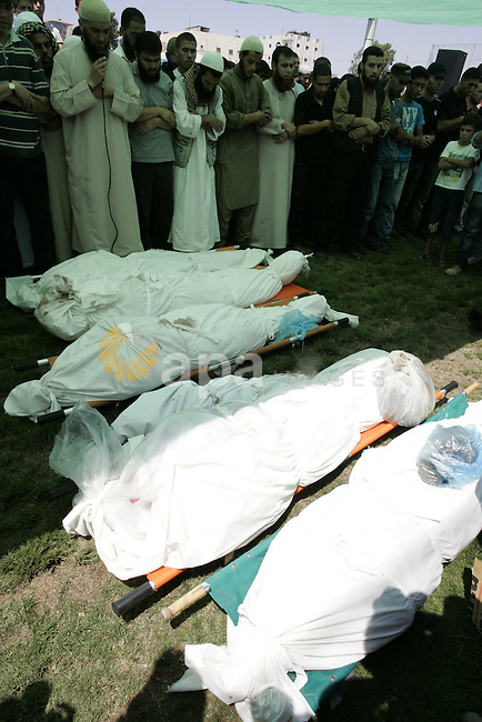 Palestinians pray near the bodies of people killed in Israeli air strikes during a funeral in the Rafah refugee camp, southern Gaza Strip, on August 19, 2011. Israeli fighter jets bombed Gaza, killing a teenager and injuring five people, in retaliation to a series of coordinated attacks on August 18 near the southern Israeli sea resort of Eilat that left eight dead. Photo by Abed Rahim Khatib