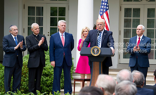 United States President Donald J. Trump makes remarks prior to signing a Proclamation designating May 4, 2017 as a National Day of Prayer and an Executive Order &quot;Promoting Free Speech and Religious Liberty&quot; in the Rose Garden of the White House in Washington, DC on Thursday, May 4, 2017.  From left to right: Rabbi Marvin Hier, president Simon Wiesenthal Center; Cardinal Donald Wuerl, the archbishop of Washington; Pastor Jack Graham; Pastor Paula White of Florida&rsquo;s New Destiny Christian Center; President Trump; US Vice President Mike Pence.<br /> Credit: Ron Sachs / CNP
