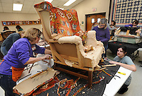 NWA Democrat-Gazette/ANDY SHUPE<br /> Kayla Clark (from right) of Fayetteville and her mother, Deborah Clark, work together Wednesday, Feb. 15, 2017, with expert local upholsterer Bonnie Williams to remove old material and padding from a decades-old wingback chair during the first day of an upholstery class at the Washington County Cooperative Extension Office in Fayetteville. The class has been led by the Washington County Extension Home Furnishers since 2000 and accompanies other instruction that the group provides to residents. Ten students receive expert assistance and instruction from a large group of volunteers as they learn to upholster a chair that they bring from home.