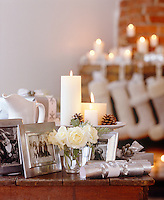 Candlelight flickers on the mantelpiece where a row of Christmas stockings hangs expectantly while in the foreground a table of silver-framed photographs is illuminated by more candles