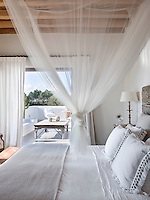 Looking from the bedroom across the bed with mosquito net to the private terrace with views over the surrounding countryside