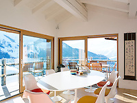 Floor to ceiling sliding windows surround the dining area and provide spectacular mountain views