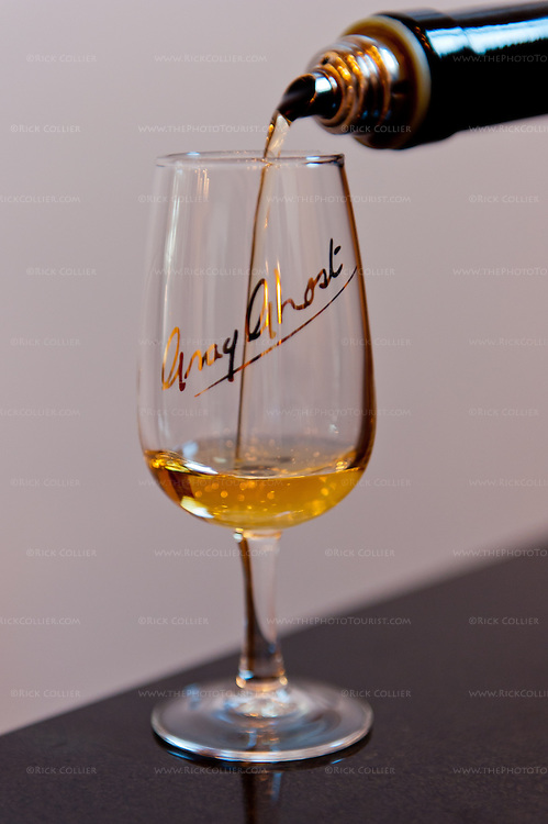 A taste of golden-colored desert wine is poured into my glass at Gray Ghost Vineyards.