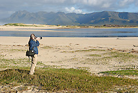 Man taking photograph of a landscape with telephoto in the morning, Flamingo lake estuary near Hermanus, South Western Cape, South Africa
