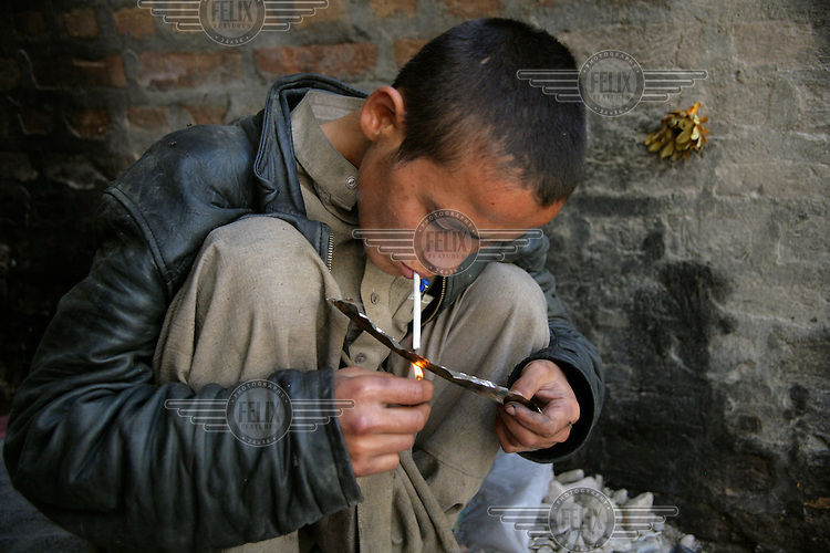 A boy smokes heroin outside the De Las Gul centre for drug users. UNICEF assisted with the establishment of the centre, and provides medical treatment, washing facilities and clean needles to addicts young and old. The centre also provides STD and HIV testing, and provides detox therapy alongside recreational activities. .
