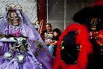 A couple rest during a rosary ceremony behind two Sante Muerte figures that are for sale in Tipito, Mexico City.