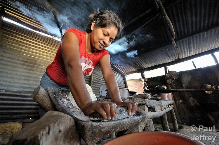 A woman grinds corn as she prepares tortillas in her home in Santa Catarina Masahuat, El Salvador.