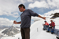 A worker holds a safety line to a worker on Brunnenkogel Ferner.  It is wrapped with a fleece-like cover to keep it from melting.  Workers attached it to the top of the part of the glacier.  Covered ice melts slower. <br /> The ski area at 3,400 meters is covered to help save the ski industry since the glacier is retreating.  The cost of materials is one Euro per square meter.<br /> <br /> The Alpine glaciers -- in Austria, Switzerland, France and Italy -- are losing one percent of their mass every year and, even supposing no acceleration in that rate, will have all but disappeared by the end of the century. More hot, dry summers like that of 2003 in Europe, when the loss speeded to five percent, could cut the life expectancy to no more than 50 years, according to Wilfried Haeberli of the University of Zurich...&quot;We estimate that by the end of the 21st century, with a medium-type climate scenario, about five percent of what existed in the 1970s will have survived, he added.