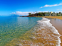 View of Ka'anapali Beach with black rock and the Sheraton Resort in the distance.