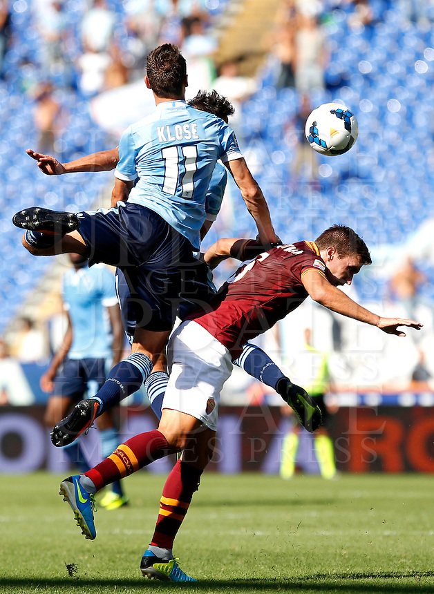 Calcio, Serie A: Roma vs Lazio. Roma, stadio Olimpico, 22 settembre 2013.<br /> Lazio forward Miroslav Klose, of Germany, left, and AS Roma midfielder Kevin Strootman, of the Netherlands, jump for the ball during the Italian Serie A football match between AS Roma and Lazio, at Rome's Olympic stadium, 22 September 2013.<br /> UPDATE IMAGES PRESS/Isabella Bonotto