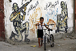 A Palestinian child plays in front of a wall graffiti, in Rafah refugee camp southern the Gaza strip, Oct. 30, 2012. In the aftermath of the Israeli military Operation Cast Lead in 2008/2009, Palestinian refugees in Gaza camps need more support to reconstruct Gaza, promote economic recovery and address the long-term development needs, including infrastructure. Photo by Eyad Al Baba