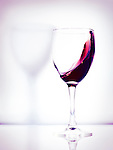 Red wine in a glass artistic photo isolated on bright white pink background