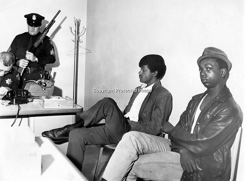 Black Panthers Bobby Seale and Bobby Hutton detained at the Oakland Police Dept. while officers check guns. Hutton was shot and killed by police shortly after this photo when he and Elridge Cleaver were involved in a shoot-out with Oakland Police. .(1967 photo by Ron Riesterer)