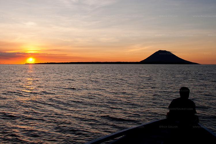 Sunset lights the sky behind Bunaken Island (foreground) and the volcano island Manado Tua beyond.  Bunaken, off North Sulawesi, Indonesia.