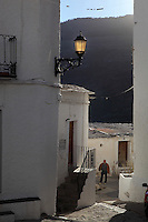 Street scene with with mountainous background, Capileira, Poqueira gorge, Alpujarra, Andalucia, Southern Spain. Moorish influence is seen in the distinctive cubic architecture of the Sierra Nevada's Alpujarra region, reminiscent of Berber architecture in Morocco's Atlas Mountains. Photograph by Manuel Cohen.