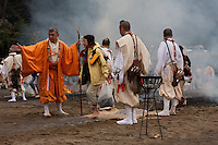 Yamabushi or mountain priests help people after they have walked over the burning embers of a  large bonfire during the Hi Watari firewalking festival, Takaosan guchi near Tokyo, Japan. Sunday March 8th 2009