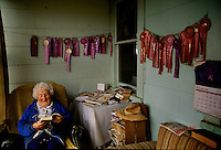 """Winner of more than 60 Humbolt County gardening prizes, 93-year old Mary Coppini relaxes on the ribbon-laden porch of her Ferndale, California home. """"There are lots more inside. I've just never hung them up,"""" she said. Mary has won the competition so many times, that the organizers no longer allow her to enter."""