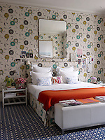 The walls of the master bedroom are covered in a striking Osborne & Little linen and the bench is by Christian Liaigre