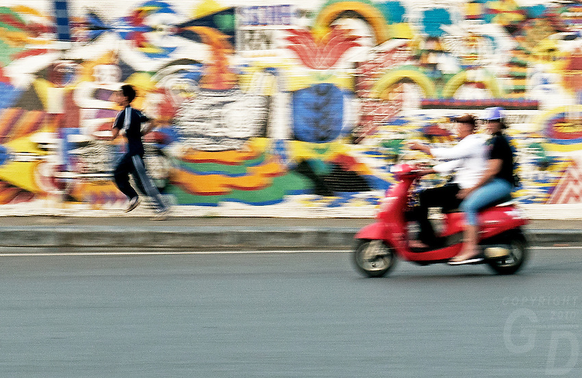 Traffic buzzes past the colorful 3.85 km long Hanoi Ceramic Mosaic Mural. It is the world's largest ceramic mosaic built from ceramic tesserae.<br /> <br /> The Hanoi Ceramic wall was built in-line with the 1000th anniversary of the foundation of the capital Thăng Long in October 2010. The whole idea of transforming a boring dyke-wall into a colorful ceramic mosaic originated because of Nguyen Thu Thuy. She is a journalist and her idea won the Hanoi Architecture Contest. The preparations to decorate the walls started in 2007. People and artists from not only Vietnam but all over the world contributed in the making of this mural. With Terracotta structures of boats, dragons, lac birds, fish, pelicans surrounded by mosaic tiles, the decorative patterns are a visual narration of the country&rsquo;s history from different periods.