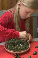 Kinder basteln Zwergengärtchen, Zwergen-Gärtchen aus Naturmaterialien, Bastelei, Tonschale wird mit Moos ausgelegt, Rinde, Eicheln, Kastanien, Äste und Blätter liegen zum Dekorieren bereit. Ein Zaun aus Ästchen wird genaut.