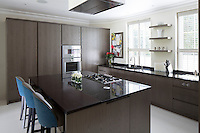 The bespoke kitchen by Mowlem, with cool grey cabinetry, incorporates concealed appliances and an island breakfast bar.