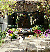 The secluded courtyard garden was designed by Kate Ewald and Amy Wilson with a Jonathan Adler garden table surrounded by a set of white wrought-iron chairs