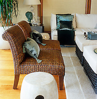 Woven seagrass armchairs accessorized with turquoise silk cushions are interesting accents in a predominantly cream colour scheme in this living room
