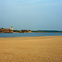 View of the traditional stilted, thatched huts of the hotel complex seen from the beach across the lagoon