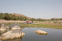 Morocco - Oasis of Fint - Women washing clothes in the river crossing the Oasis of Fint. The Oasis was the set of several well-known movies, including Lawrence of Arabia, Jesus of Nazareth, Alibaba, Moses and Cleopatra.