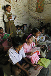 IND.MWdrv04.068.x..Seema Yadav, in pink, in her classroom at school, wasn't yet born when the Material World family portrait was taken in 1994. Ahraura Village, Uttar Pradesh, India. Revisit with the family, 2004. The Yadavs were India's participants in Material World: A Global Family Portrait, 1994 (pages: 64-65), for which they took all of their possessions out of their house for a family-and-possessions-portrait. Child, Children, Education. .