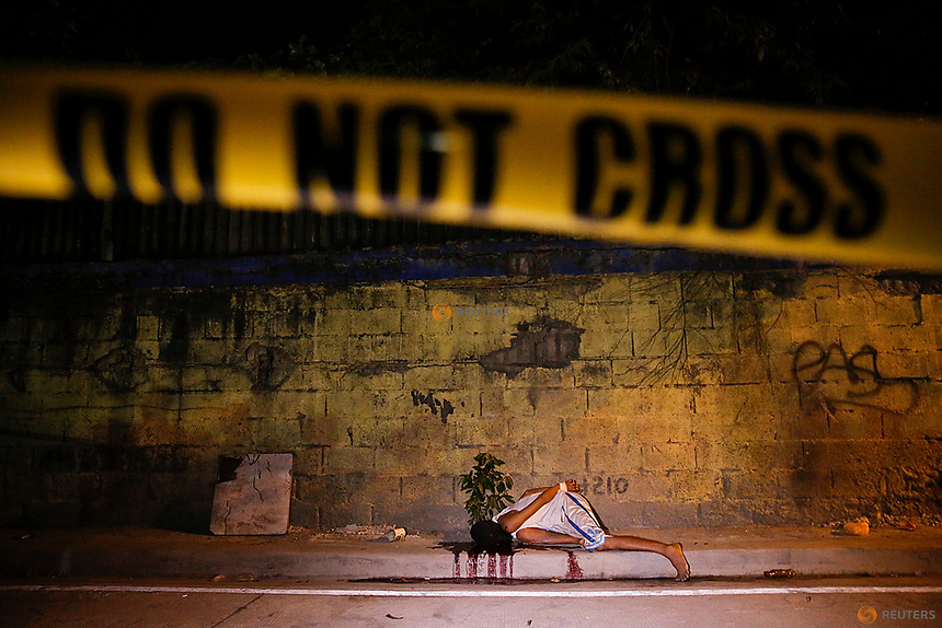 Police line is placed around the body of a man killed by unknown gunmen in Manila, Philippines early October 25, 2016. REUTERS/Damir Sagolj