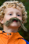 Boy in a Norwegian naturbarnehagen (nature nursery) with a lichen moustache