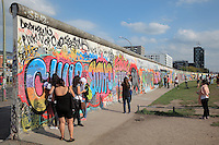 Tourists visiting a section of the Berlin Wall covered in graffiti, part of the East Side Gallery, a 1.3km long section of the Wall on Muhlenstrasse painted in 1990 on its Eastern side by 105 artists from around the world, Berlin, Germany. Picture by Manuel Cohen