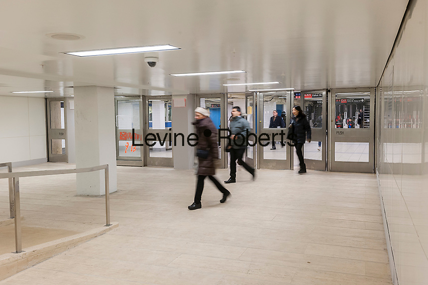 """Commuters and other travelers pass through the newly opened World Trade Center connecting passageway in New York on Monday, December 19, 2016. The passage, which connects the Chambers Street subway station with the WTC Oculus and further on the PATH station, is a vestige from the original World Trade Center, destroyed in the terrorist attack on Sept. 11, 2001. The ramp and the travertine flooring are original as well as a commemorative door, labeled """"MATF1 9-13"""" indicating the area was searched by the Massachusetts Task Force 1 Urban Search and Rescue Team on September 13. (© Richard B. Levine)"""