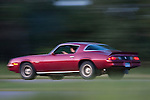 A Camaro or Trans Am drives quickly down a freeway.