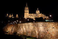General view, Cathedral, Salamanca, Spain, pictured on December 19, 2010 at night, floodlit with the Roman bridge in the foreground. Salamanca, Spain's most important University city,  has two adjoining Cathedrals, Old and New. The old Romanesque Cathedral was begun in the 12th century, and the new in the 16th century. Its style was designed to be Gothic rather than Renaissance in keeping with its older neighbour, but building continued over several centuries and a Baroque cupola was added in the 18th century. Restoration was necessary after the great Lisbon earthquake, 1755. Picture by Manuel Cohen