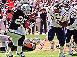 Oakland Raiders vs. San Diego Chargers at Oakland Alameda County Coliseum Sunday, September 3, 2000.  Raiders beat Chargers  9-6.  Oakland Raiders running back Napoleon Kaufman (26) attempts to out run San Diego Chargers defensive end Albert Fontenot (95).