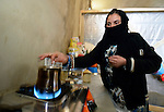 A Syrian refugee woman prepares tea in a rented storefront where she and her family live in Kamid al lawz, a town in Lebanon's Bekaa Valley. The International Orthodox Christian Charities and other members of the ACT Alliance are assisting refugees here in a variety of ways..