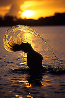 Woman flipping her wet hair in the ocean backlit by the sunset<br />