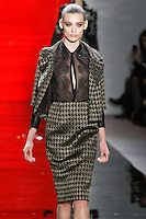 Carolina walks runway in a ebony metallic herringbone bracelet-sleeve jacket over ebony chiffon and lace blouse with leather collar and cuffs and ebony metallic herringbone pencil skirt, from the Reem Acra Fall 2012 Feminine Power collection fashion show, during Mercedes-Benz Fashion Week New York Fall 2012 at Lincoln Center.