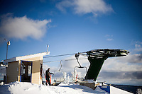 A lift operator watches the top of a chairlift at Showdown Ski Area on King's Hill in the Little Belt Mountains near Neihart, Montana, USA.