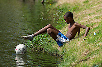 A kid fetches his football out of the water