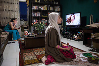 A woman prays while her friend is smoking and watching television.
