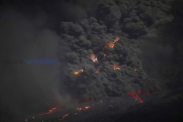 Glowing pyroclastic flow decending flank of Sinabung Volcano at night with volcanic lightning, Sumatra, Indonesia