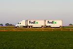 A tractor toting two FedEx Freight trailers behind is speeding down I-57 in east central Illinois. FedEx Freight is a bulk delivery subsidiary of FedEx, the popular parcel delivery company.