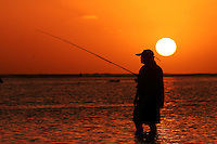 Fisherman patiently waits for fish to bite at Ala Moana Park just before sunset.