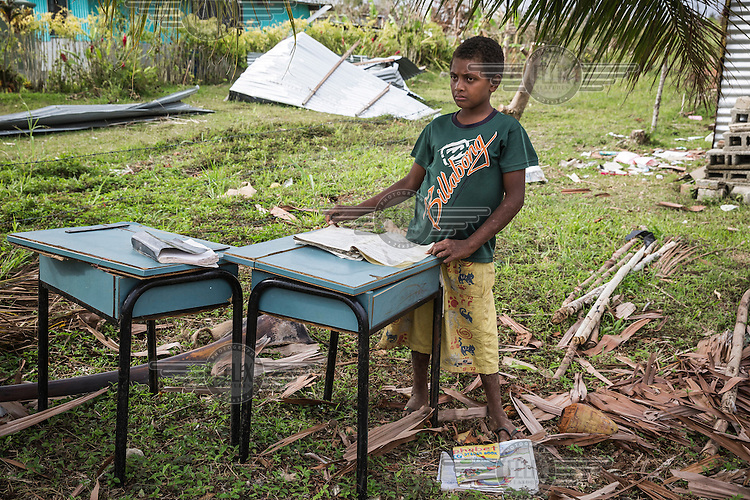 10 year old James with some broken desks, some of the few remains of his school in Etas village. It was destroyed by Cyclone Pam on 13 March 2015. He says: 'I was in a community shelter with my parents. When the strong wind came it was very noisy, I was afraid. Then my sisters and I fell asleep. Next morning we came to our house and it was destroyed. My school was destroyed too. Now I sleep with my parents in a tent and can't attend classes'.